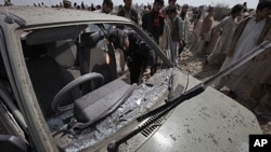 A police officer and local residents examine a parked car damaged in a suicide bombing at a funeral on the outskirts of Peshawar, Pakistan, Sunday, March 11, 2012.