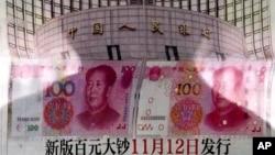 北京有人在街头报栏阅读报纸上关于中国央行宣布将发行百元新钞的消息(2015年8月11日)