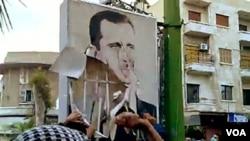 Demonstran anti-pemerintah menyobek potret Presiden Bashar al-Assad di kota Hama dalam unjuk rasa Jumat (29/4).
