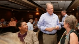 Democratic Senate nominee Doug Jones, center, talks to supporters, Jennifer L. Greer, right, and Janet Crosby, left, as he campaigns at Niki's West restaurant, Wednesday, Sept. 27, 2017, in Birmingham, Alabama.