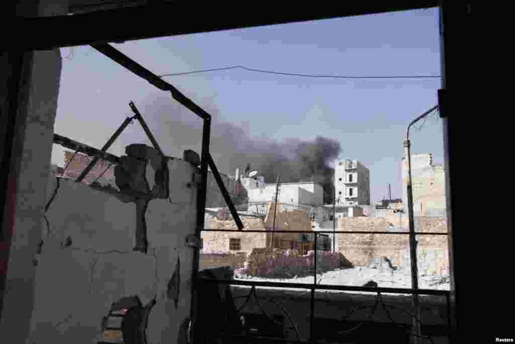 Smoke rises from behind buildings after a shelling at Karm al-Jabal in northeast Aleppo, Syria, October 19, 2012.