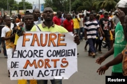 "FILE - A man holds up a sign, which reads: ""Faure still how many death by you,"" during an opposition protest calling for the immediate resignation of President Faure Gnassingbe in Lome, Togo, Sept. 6, 2017."