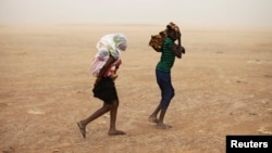Women wrapped in shawls walk through a sandstorm in Timbuktu, July 29, 2013.