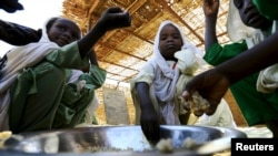 FILE - Internally displaced schoolchildren eat from the same bowl during a feeding program provided by the World Food Program at the Abushouk camp in Al Fasher in North Darfur, Sudan, Nov. 17, 2015.
