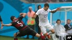 Foutbolè alman Mats Hummels, agòch, ak ameriken Fabian Johnson ap goumen pou balon an nan yon match gwoup G a ki dewoule nan vil Recife. (Foto: 26 jen 2014).