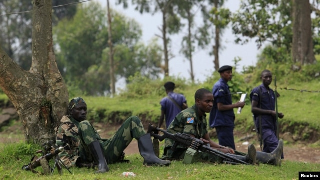 M23 rebel fighters watch the venue of a news conference by political leader Jean-Marie Runiga, in Bunagana, eastern DRC, in north Kivu province, July 21, 2012.