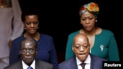 FILE: Zimbabwe's President Robert Mugabe, front left, and South Africa's President Jacob Zuma, front right, enter the Union building in Pretoria, April 8, 2015. Also pictured are Zimbabwe's first lady Grace Mugabe, rear left, and South Africa's first lady.