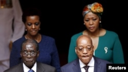 Zimbabwe's President Robert Mugabe, front left, and South Africa's President Jacob Zuma, front right, enter the Union building in Pretoria, April 8, 2015. Also pictured are Zimbabwe's first lady Grace Mugabe, rear left, and South Africa's first lady Thobe