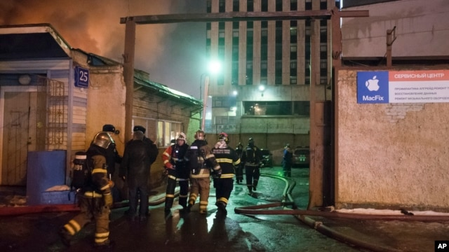 In this photo taken late Jan.  30, 2016, firefighters prepare to work to extinguish a fire at a textile workshop in Moscow, Russia. Russian officials say a fire at a textile workshop in Moscow has killed more then dozen people, including three children.