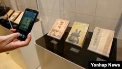 19일 한국 은평역사한옥박물관에서 열린 '한국문학 속의 은평전' 사전설명회에서 한 시민이 문학작품 초판본을 휴대전화로 촬영하고 있다.