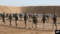 Soldados estadounidenses ayudando a fuerzas de seguridad iraquíes a mejorar sus habilidades de tiro en TAji, al norte de Bagdad, Irak.