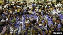 Migrants believed to be Rohingya rest inside a shelter after being rescued from boats at Lhoksukon in Indonesia's Aceh Province May 11, 2015. (REUTERS/Roni Bintang)