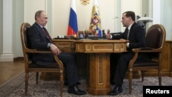 Russian President Vladimir Putin (L) meets with Prime Minister Dmitry Medvedev at the Novo-Ogaryovo state residence outside Moscow, March 27, 2014.