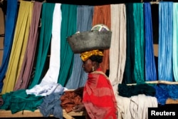 FILE - A woman carries a bucket on her head as she walks past fabrics for sale in Gao, Mali, Feb. 2013.