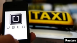 Layar ponsel dengan logo aplikasi Uber di samping lambang taksi di Frankfurt, Jerman.