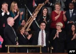 川普總統國情咨文演說特邀嘉賓池成鎬在川普演說中提到他時站起身來揮舞拐杖致意。(2018年1月30日)