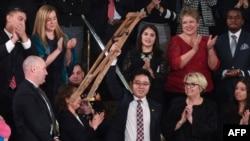 川普总统国情咨文演说特邀嘉宾池成镐在川普演说中提到他时站起身来挥舞拐杖致意。(2018年1月30日)