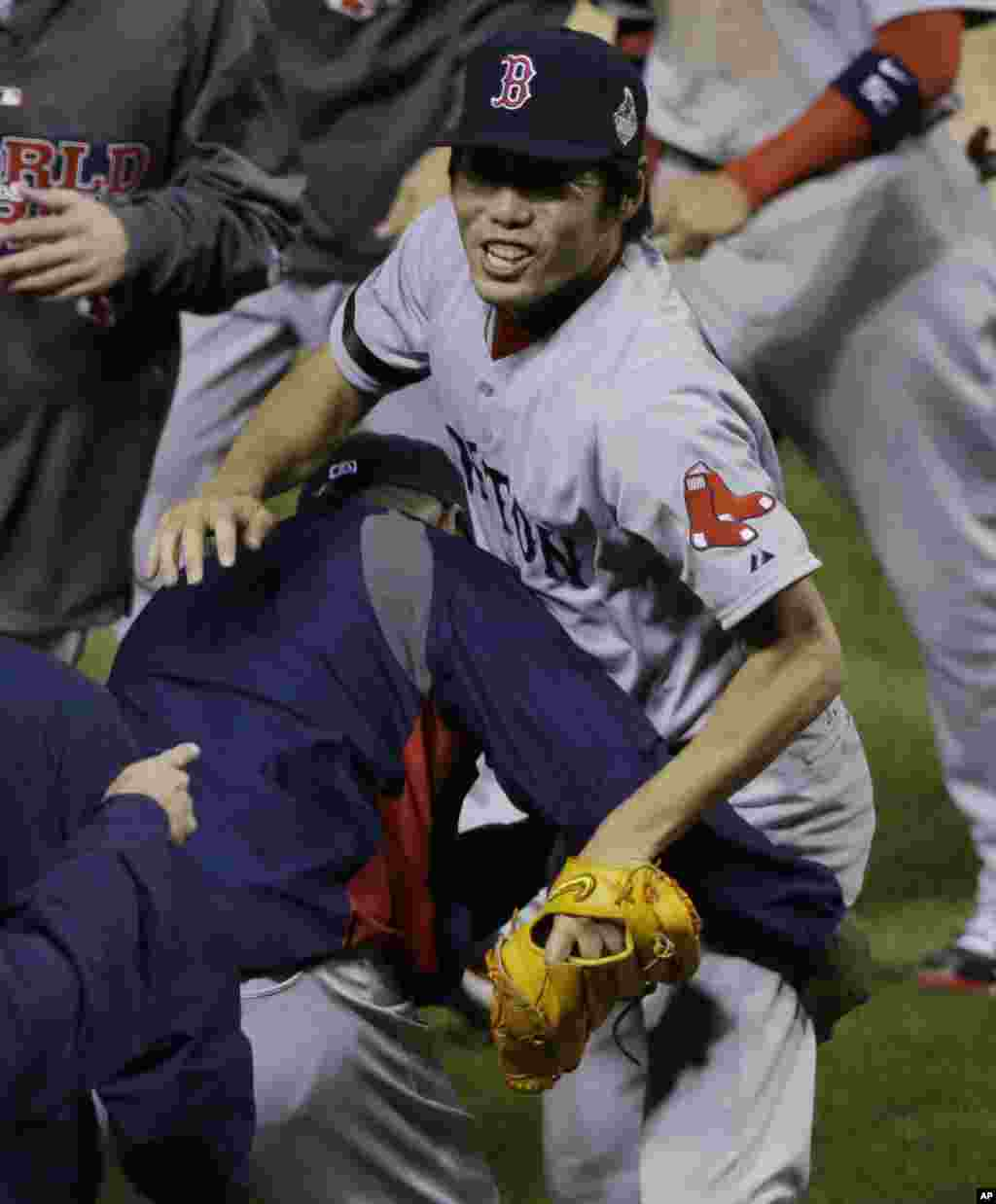 Boston Red Sox relief pitcher Koji Uehara, right, celebrates after picking off St. Louis Cardinals Kolten Wong at first base to end Game 4 of baseball's World Series, Oct. 27, 2013, in St. Louis.