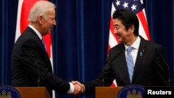 U.S. Vice President Joe Biden (L) shakes hands with Japan's Prime Minister Shinzo Abe at the end of their joint news conference following their meeting at the prime minister's official residence in Tokyo, Dec. 3, 2013. Biden urged Japan and China to lower