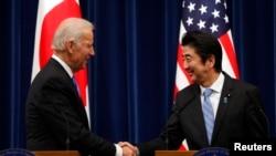 美国副总统拜登(左)和日本首相安倍晋三12月3日在东京举行联合记者会后握手。