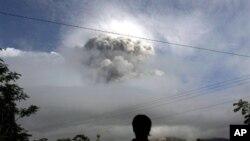 Wani dan kasar Indonesia yake kallon Dutsen Merapi lokacinda yake aman wuta