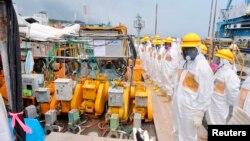 2013年8月6日穿上防護衣的人員在日本福島第一核電站檢測懷疑核污染水洩漏。