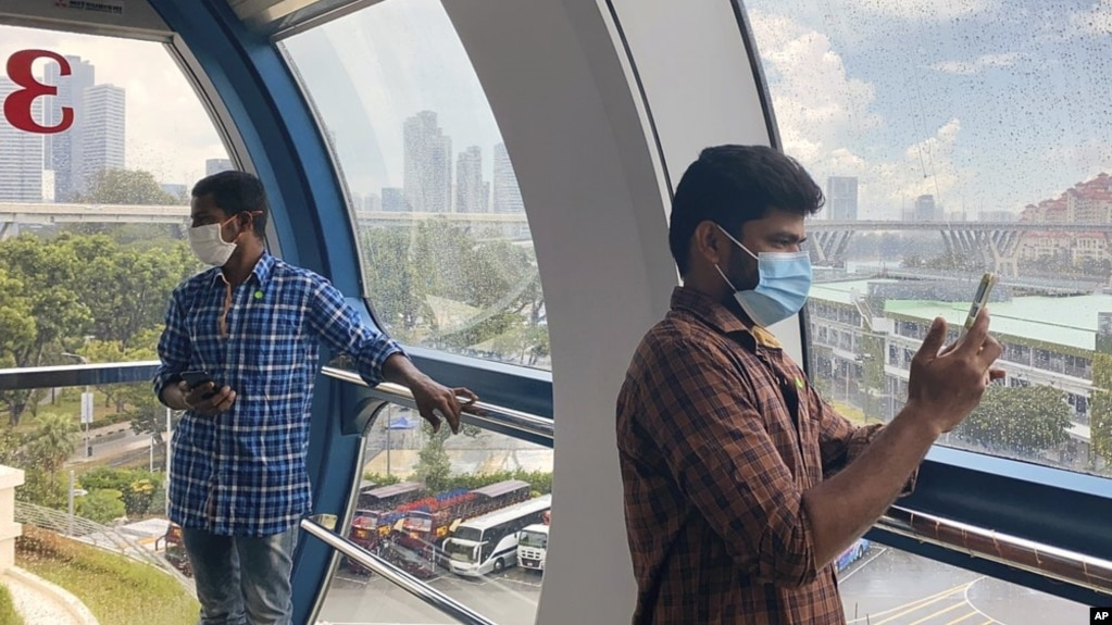 Migrant worker Natarajan Pandiarajan, right, enjoys the view on board the Singapore Flyer attraction in Singapore on March 7, 2021. (AP Photo/Annabelle Liang)
