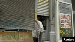 "A man prepares to leave his shop next to an empty one with a sign reading ""For Rent"" in Piraeus port-town near Athens, May 29, 2012."