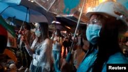 Протестующие стоят под проливным дождем, блокируя главное шоссе в торговом районе Монгкок в Гонконге. 22 октября 2014 г.
