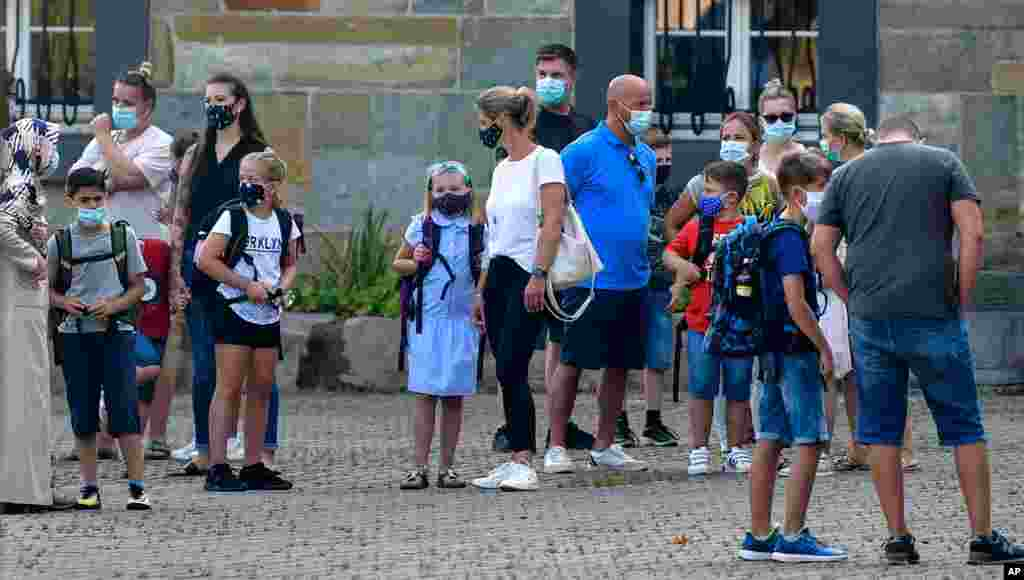 گروهی از خانوادهها به همراه فرزندانشان در نخستین روز بازگشایی مدارس در شهری در آلمان.
