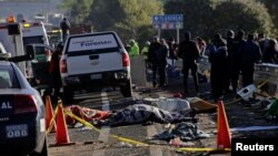FILE - Police officers and rescue personnel stand near the bodies of people who were killed in a car crash on the outskirts of Puebla, Mexico, Dec. 12, 2017.