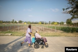 Sampao Jantharun (L), 78, assists Somjit Phuthasiri, 90, on a wheelchair as they head to their home at Wellness Nursing Home Center in Ayutthaya, Thailand, April 9, 2016.