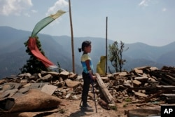 In this April 8, 2016 photo, Khendo Tamang, 8, stands near the debris of the collapsed home she was trapped in after the April 25, 2015 earthquake struck in Banskharka, Nepal.