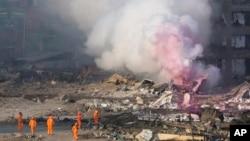 Bomberos en trajes protectores observan humo parcialmente rosado saliendo de las explosiones en un depósito en el noreste de China.
