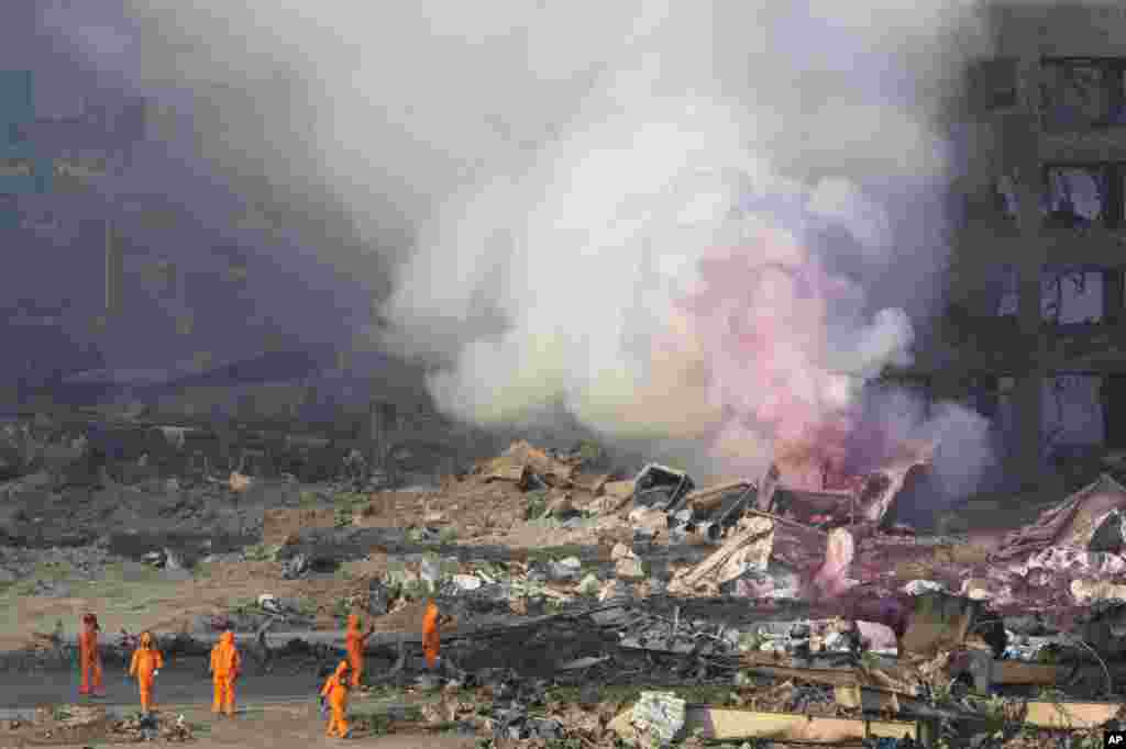 Firefighters in protective gear stand by as pink smoke billows up into the sky after an explosion at a warehouse in northeastern China's Tianjin municipality, Aug. 13, 2015.