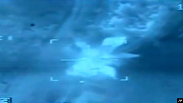 FILE - An image taken from aerial footage shows a target hit by an airstrike in Libya.