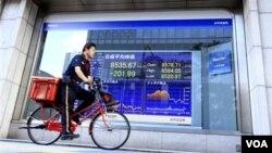 Petugas pos melintasi papan saham elektronik di Tokyo (12/9). Rata-rata saham Jepang mencapai titik terendah sejak April 2009.