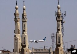 FILE - In this May 21, 2016, file photo, an EgyptAir plane flies past minarets of a mosque as it approaches Cairo International Airport, in Cairo, Egypt.