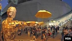 在香港政府總部外擺放的民間藝術家製作的巨型撐傘人體塑像。(圖片來源: 香港蘋果日報網站)