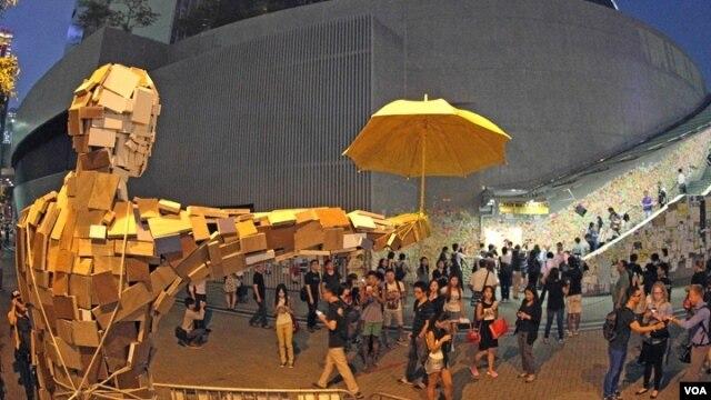 Bức tượng người đàn ông cầm cây dù được dựng lên tại địa điểm nơi họ dựng trại. Tuần trước những người biểu tình đã dùng những chiếc dù để tự vệ chống lại cảnh sát sử dụng hơi cay