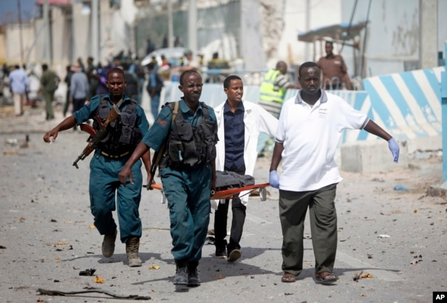 United Nations office guards and Somalian soldiers carry the dead body of their colleague who was killed in a suicide car bomb outside the UN's office in Mogadishu, Somalia on July 26, 2016