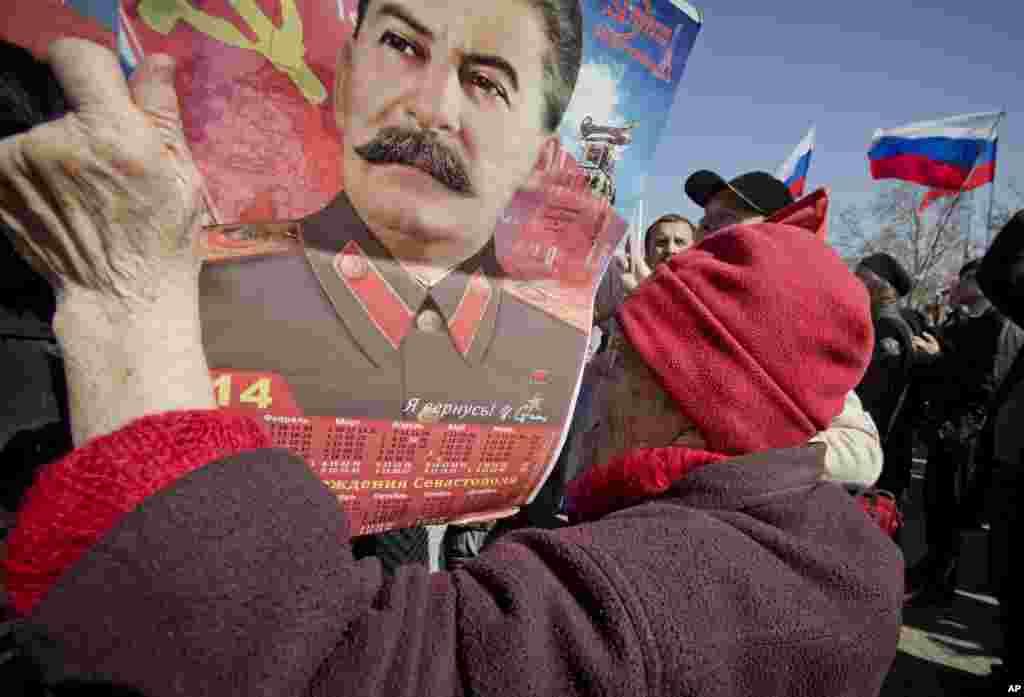 An elderly woman holds a calendar depicting Soviet leader Josef Stalin while watching a broadcast of Russian President Vladimir Putin's speech on Crimea, as thousands of pro-Russian people gathered to watch the address, in Sevastopol,Crimea, Ukraine, March 18, 2014.