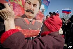 在普京就克里米亚问题发表电视讲话时,有俄罗斯老人举起带有斯大林像的挂历