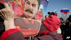 An elderly woman holds a calendar depicting Soviet leader Josef Stalin while watching a broadcast of Russian President Vladimir Putin's speech on Crimea in Sevastopol, Crimea, Tuesday, March 18, 2014.