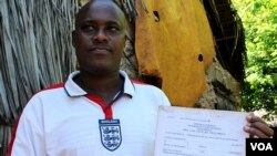 Felix Karisa hold up the notice ordering the eviction of his entire village outside Mombasa, Kenya, November 18, 2012. (H. Heuler/VOA)