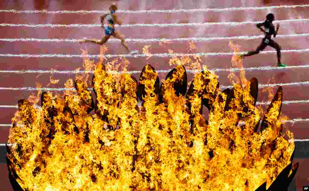 August 3: Runners pass by the Olympics flame on the first day of the athletics in the Olympic Stadium at the 2012 Summer Olympics in London.