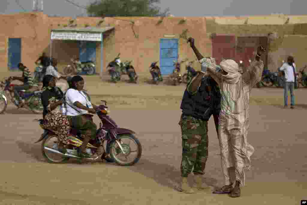 A man is patted down by a United Nations peacekeeper outside the main polling place in Kidal, Mali, July 28, 2013.