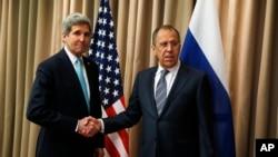 Menlu AS John Kerry (kiri) berjabat tangan dengan Menlu Rusia Sergey Lavrov di sela-sela pertemuan di Jenewa, Swiss hari Kamis (17/4).