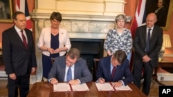 Britain's Prime Minister Theresa May, second right, stands with First Secretary of State Damian Green, right, Democratic Unionist Party leader Arlene Foster, second left, and DUP Deputy Leader Nigel Dodds as DUP MP Jeffrey Donaldson, sitting left, and Government Chief Whip Gavin Williamson sign documents inside 10 Downing Street in London, June 26, 2017.