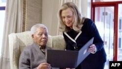 ລັດຖະມົນຕີຕ່າງປະເທດສະຫະລັດ ທ່ານນາງ Hillary Rodham Clinton ພົບປະກັບທ່ານ Nelson Mandela, ອາຍຸ 94 ປີ, ອະດີດປະທານາທິບໍດີອາຟຣິກາໃຕ້ ທີ່ເຮືອນຂອງທ່ານ ຢູ່ບ້ານ Qunu, ປະເທດອາຟຣິກາໃຕ້, ວັນທີ 6 ສິງຫາ 2012.